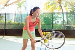 Jugador de tenis asiático hermoso que celebra la estafa y la bola antes de servir imagen de archivo libre de regalías