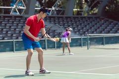 Jugador de tenis asiático listo para servir al principio de un partido de los dobles fotografía de archivo