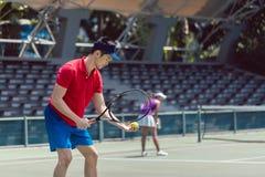 Jugador de tenis asiático listo para servir al principio de un partido de los dobles imagenes de archivo