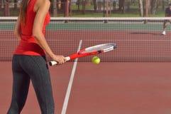 Jugador de tenis con la estafa lista para servir una pelota de tenis Imágenes de archivo libres de regalías