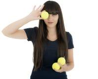 Jugador de tenis de la mujer que celebra una estafa y las bolas, aisladas en un wh Foto de archivo