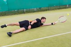 Jugador de tenis de sexo masculino en la acción durante el juego caido en una corte Fotografía de archivo libre de regalías