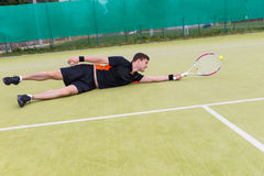 Jugador de tenis de sexo masculino hermoso en la acción durante el juego caido encendido Fotografía de archivo libre de regalías