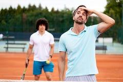 Jugador de tenis decepcionado que juega a tenis en corte imagenes de archivo