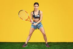 Jugador de tenis deportivo hermoso de la mujer joven listo al tiro la bola con la estafa roja sobre fondo amarillo imagenes de archivo