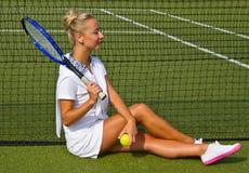 Jugador de tenis hermoso de la muchacha que se sienta en kort del entrenamiento Imagenes de archivo
