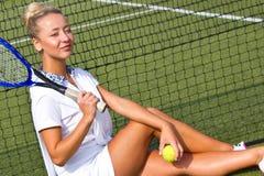 Jugador de tenis hermoso de la muchacha que se sienta en kort del entrenamiento Foto de archivo