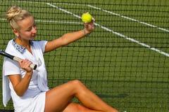 Jugador de tenis hermoso de la muchacha que se sienta en kort del entrenamiento Fotografía de archivo
