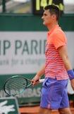 Jugador de tenis profesional Bernard Tomic de Australia en la acción el suyo durante el primer partido de la ronda en Roland Garr Foto de archivo