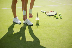 Jugador de tenis que ata los zapatos de los deportes antes de la práctica Imagenes de archivo