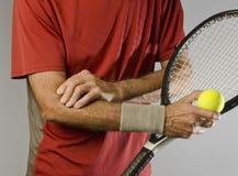 Jugador de tenis que da masajes al codo Foto de archivo