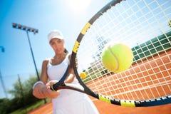 Jugador de tenis que golpea la bola Imagen de archivo libre de regalías