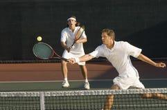 Jugador de tenis que golpea la bola con el socio de los dobles que se coloca en fondo Fotos de archivo