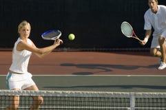 Jugador de tenis que golpea la bola con el socio que se coloca en fondo Fotografía de archivo libre de regalías