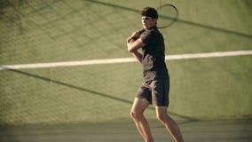 Jugador de tenis que juega en un hardcourt almacen de metraje de vídeo
