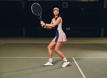 Jugador de tenis de sexo femenino en la acción en un campo de tenis interior Fotos de archivo libres de regalías
