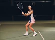 Jugador de tenis de sexo femenino en la acción en un campo de tenis interior Fotos de archivo