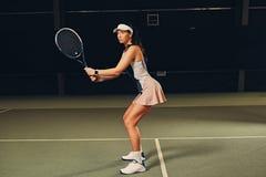 Jugador de tenis de sexo femenino en la acción en un campo de tenis interior Fotografía de archivo