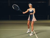 Jugador de tenis de sexo femenino en la acción en un campo de tenis interior Fotografía de archivo libre de regalías