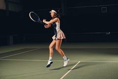 Jugador de tenis de sexo femenino en la acción en un campo de tenis interior Foto de archivo