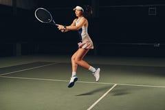 Jugador de tenis de sexo femenino en la acción en un campo de tenis interior Imagen de archivo