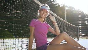 Jugador de tenis de sexo femenino que sonríe en la cámara mientras que se sienta en una pista de tenis cerca de red almacen de metraje de vídeo