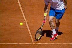 Jugador de tenis de sexo masculino en la acción en la corte en un día soleado fotografía de archivo