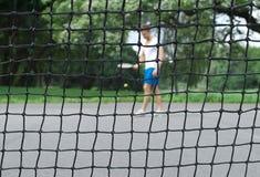 Jugador de tenis visto a través de la red Imagen de archivo libre de regalías