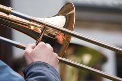 Jugador de trombón de una orquesta de cobre amarillo con la reflexión en MU Foto de archivo