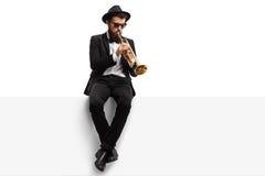 Jugador de trompeta que se sienta en un panel imagen de archivo