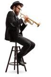 Jugador de trompeta que se sienta en una silla imagen de archivo libre de regalías