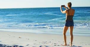 Jugador de voleibol femenino que hace clic las fotos con el teléfono móvil 4k almacen de metraje de vídeo