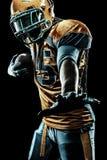 Jugador del deportista del fútbol americano aislado en fondo negro foto de archivo