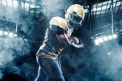 Jugador del deportista del fútbol americano en el estadio que corre en la acción Foto de archivo