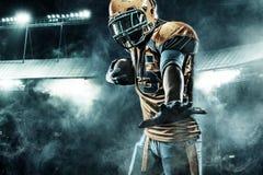 Jugador del deportista del fútbol americano en el estadio que corre en la acción Imagen de archivo libre de regalías