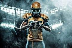 Jugador del deportista del fútbol americano en estadio con las luces en fondo