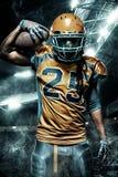 Jugador del deportista del fútbol americano en estadio con las luces en fondo fotos de archivo