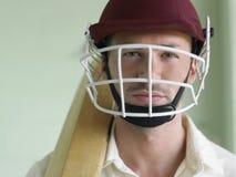 Jugador del grillo en casco y con el palo Foto de archivo