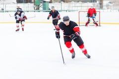 Jugador del hockey sobre hielo con el palillo que patina en la pista Foto de archivo libre de regalías