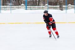 Jugador del hockey sobre hielo con el palillo que patina en la pista Foto de archivo