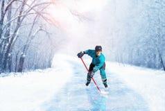 Jugador del hockey sobre hielo en uniforme en la calzada congelada Imágenes de archivo libres de regalías