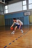 Jugador del juego de bola de la cesta en el pasillo de deporte Fotografía de archivo
