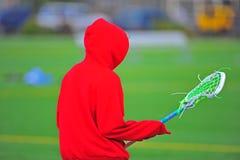 Jugador del lacrosse en un hoodie rojo Imagenes de archivo