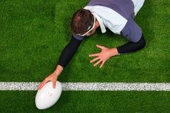 Jugador del rugbi que anota un intento con una mano Foto de archivo