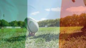 Jugador del rugbi que golpea la bola con el pie con una bandera irlandesa en el primero plano metrajes