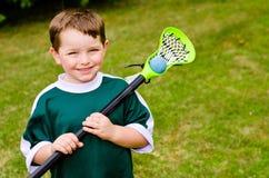 Jugador feliz del lacrosse del niño joven imagen de archivo libre de regalías