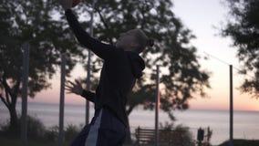 Jugador femenino del baloncesto que juega a un juego de uno en uno El jugador con el runnung y maling de la bola un aro outdoors almacen de metraje de vídeo
