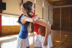 Jugador femenino sonriente que abraza en cancha de básquet Fotos de archivo