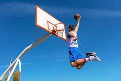 Jugador joven de la calle del baloncesto que hace clavada Foto de archivo libre de regalías