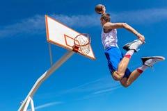 Jugador joven de la calle del baloncesto que hace clavada Fotos de archivo libres de regalías
